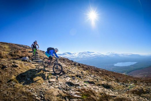 Descending under blue skies on our mountain bike tour Cairngorms