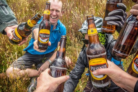 Mountain bikers enjoy a beer break in Ecuador with H+I Adventures mountain bike tour Ecuador