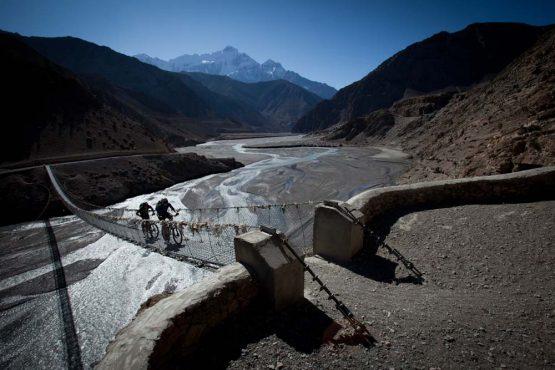 Riding across rope bridges on our mountain bike tour Nepal