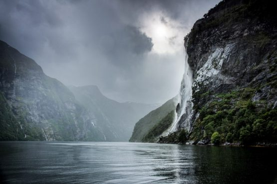 An impressive waterfall flowing down towering fjord walls on our Fjords of Norway mountain bike tour
