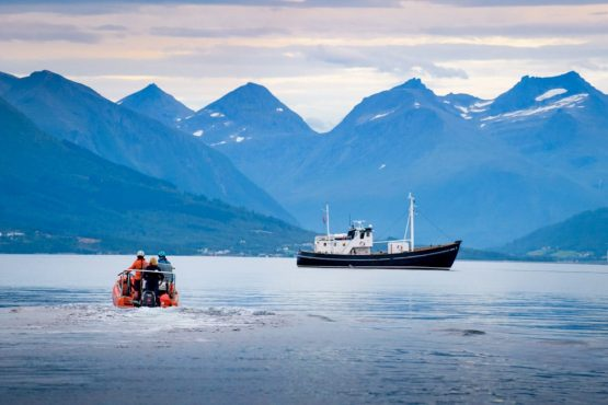 HMS Gåssten moored under the shadow of the Romsdal mountain range on our Fjords of Norway mountain bike tour
