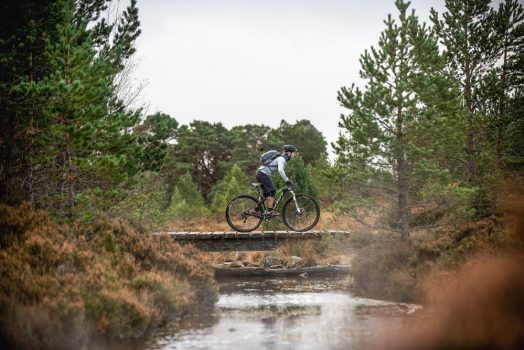 A solo rider crossing a small bridge on the mountain bike tour Cairngorms