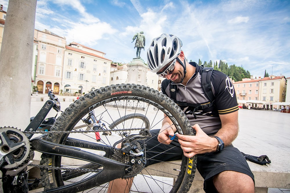 Slovenia mountain bike tour guide makes carries out some quick maintenance