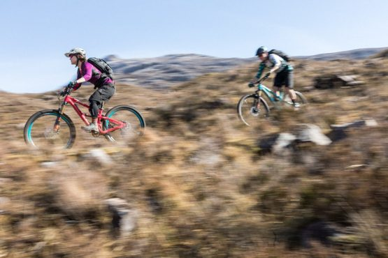 Riders descending rocky trail in Torridon mid-week on our coast-to-coast Scotland mountain bike tour