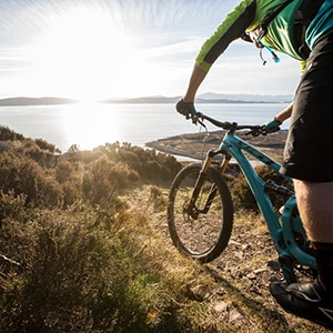 Mountain biker descending Descending on coast-to-coast mountain bike tours worldwide.