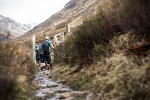 Mountain bikers passing through a gate on our mountain bike tour Torridon and Skye.