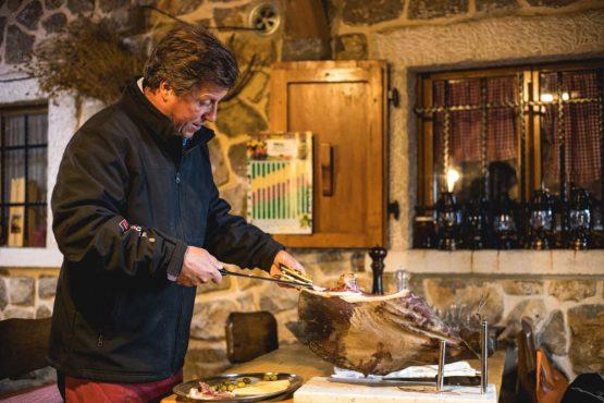 Man slices prosciutto, mountain bike tour Croatia