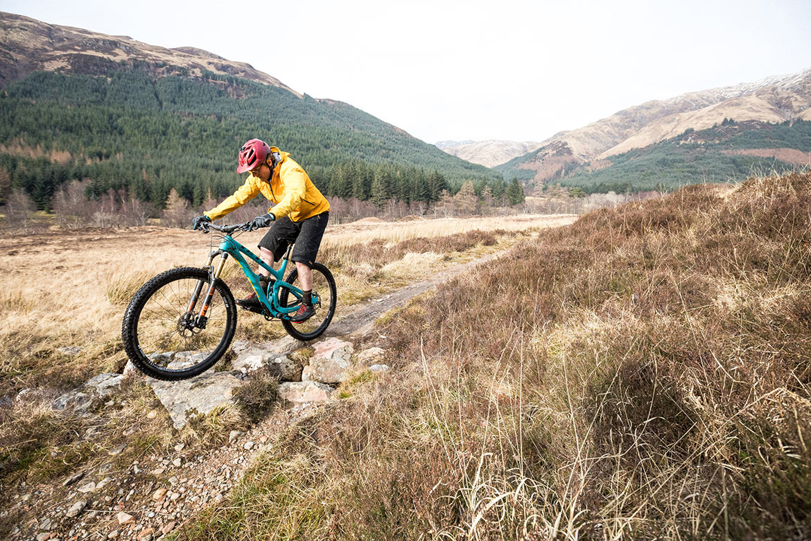 Mountain Biker riding a water bar in Torridon, Scotland, part of our How To Ride a Scottish 'Water Bar' blog.