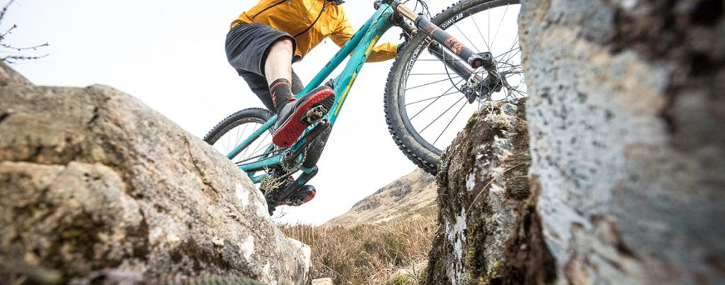 Mountain Biker riding a water bar in Torridon, Scotland, part of our How To Ride a Scottish Water Bar blog.