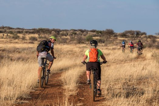 Pushing through the bush on mountain bike safari tour Namibia