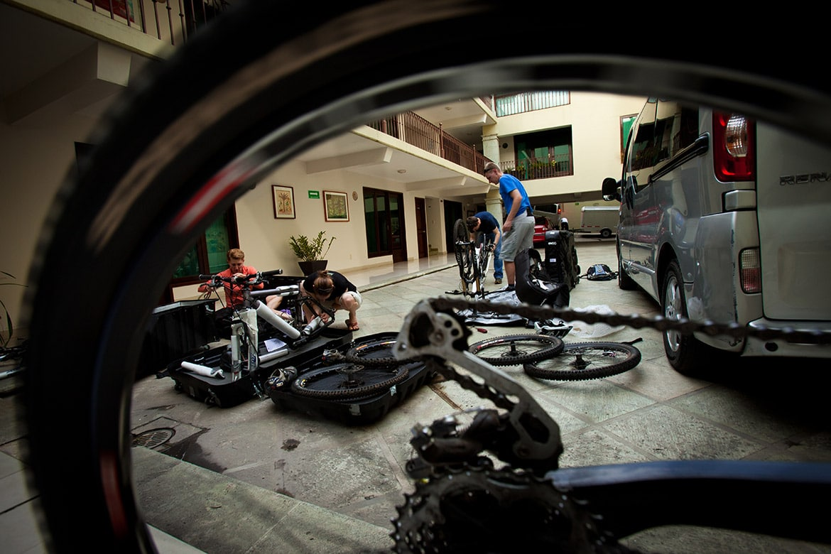 Bikers prepping bikes, part of our 5 Tips For Your First Mountain Bike Tour.