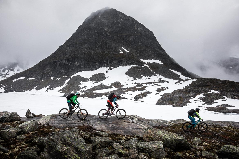 Mountain bikers dwarfed by a pyramidal peak during our mountain bike tour Norway. One of our mountain biking adventures in Europe.