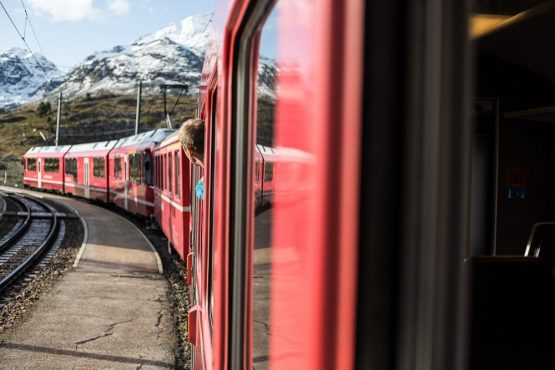 Mountain biker takes in the View from the Bernina Express, time to ride soon on our mountain bike tour Switzerland.