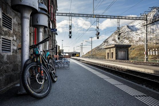Mountain bikes resting in the morning light at Ospizio Bernina train station, on our mountain bike tour Switzerland vacation