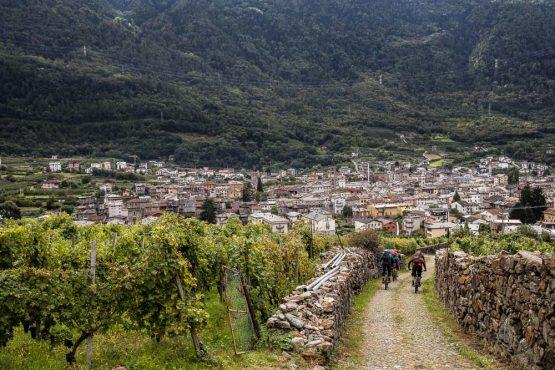 Mountain bikers descending into Italy on their mountain bike tour Switzerland adventure