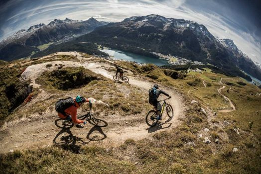 Three riders swooping down a flow trail descent to San Moritz, during H+I Adventures mountain bike tour Switzerland