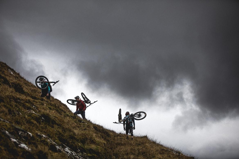Joe Barnes, Max Schumann, and Euan Wilson of H+I Adventures carry their bikes up Gleouraich.