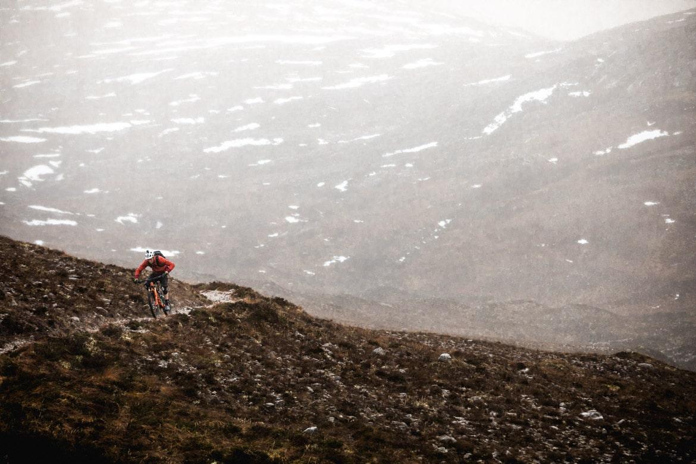 Scott Laughland descending a Scottish Highland trail in the rain.