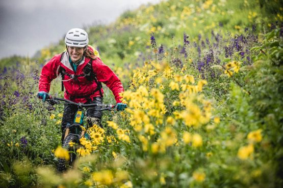 Mountain biker riding through a high alpine meadow on the 401 trail in Crested Butte, part of our mountain bike tour Colorado.