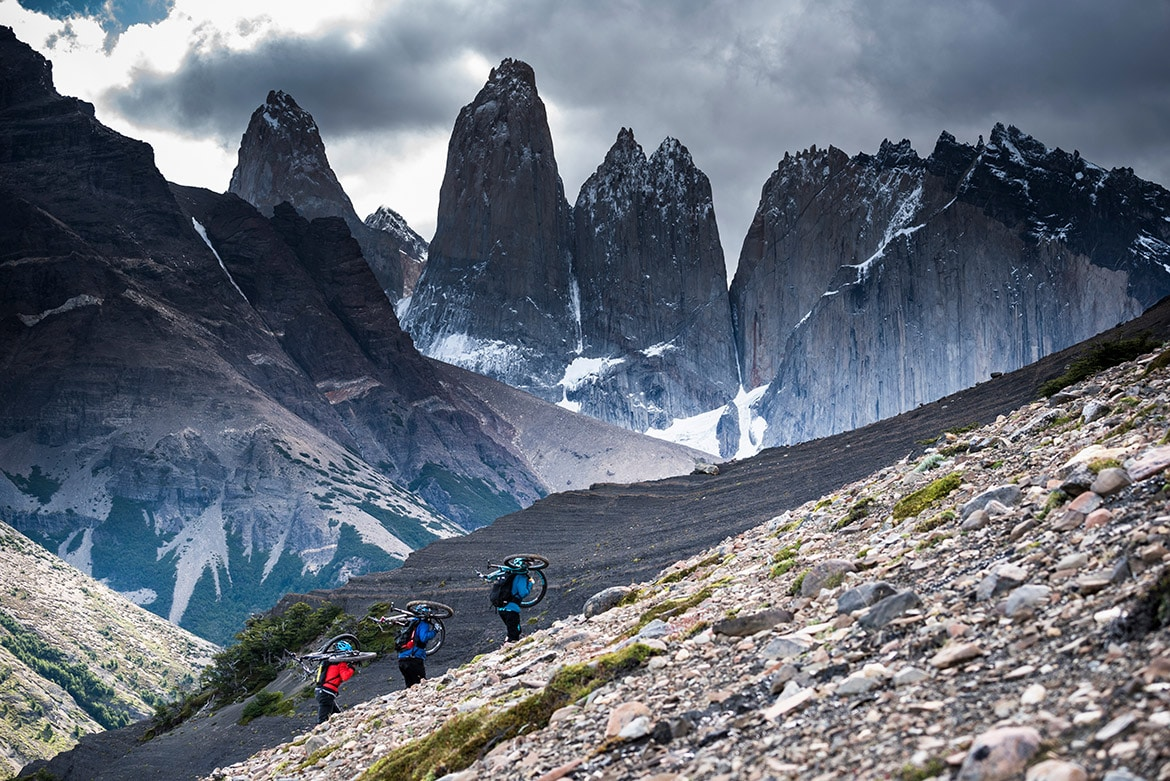 Top 10 mountain bike trails - Mountain bikers riding Cerro Paine in Chile during a mountain bike tour Patagonia.