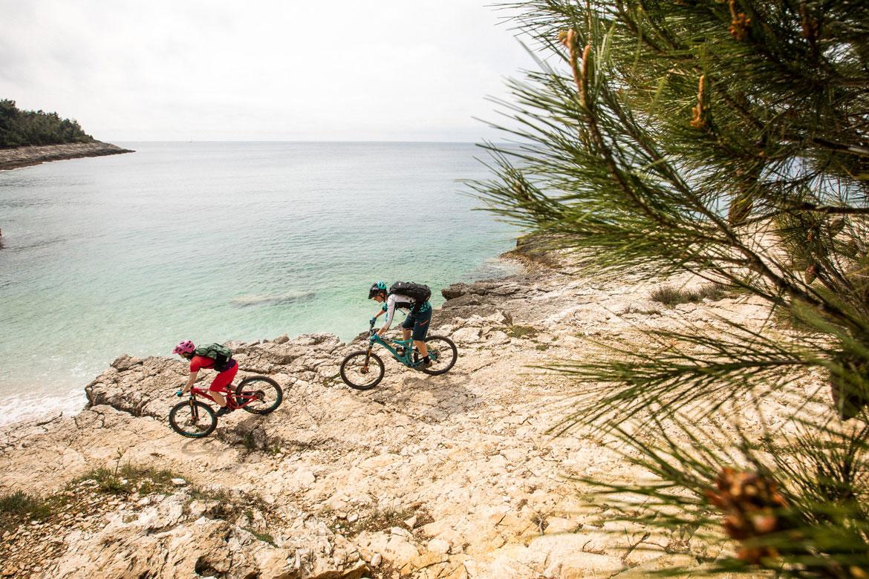 Mountain bikers descending to the sea in Croatia. One of our mountain biking adventures in Europe.