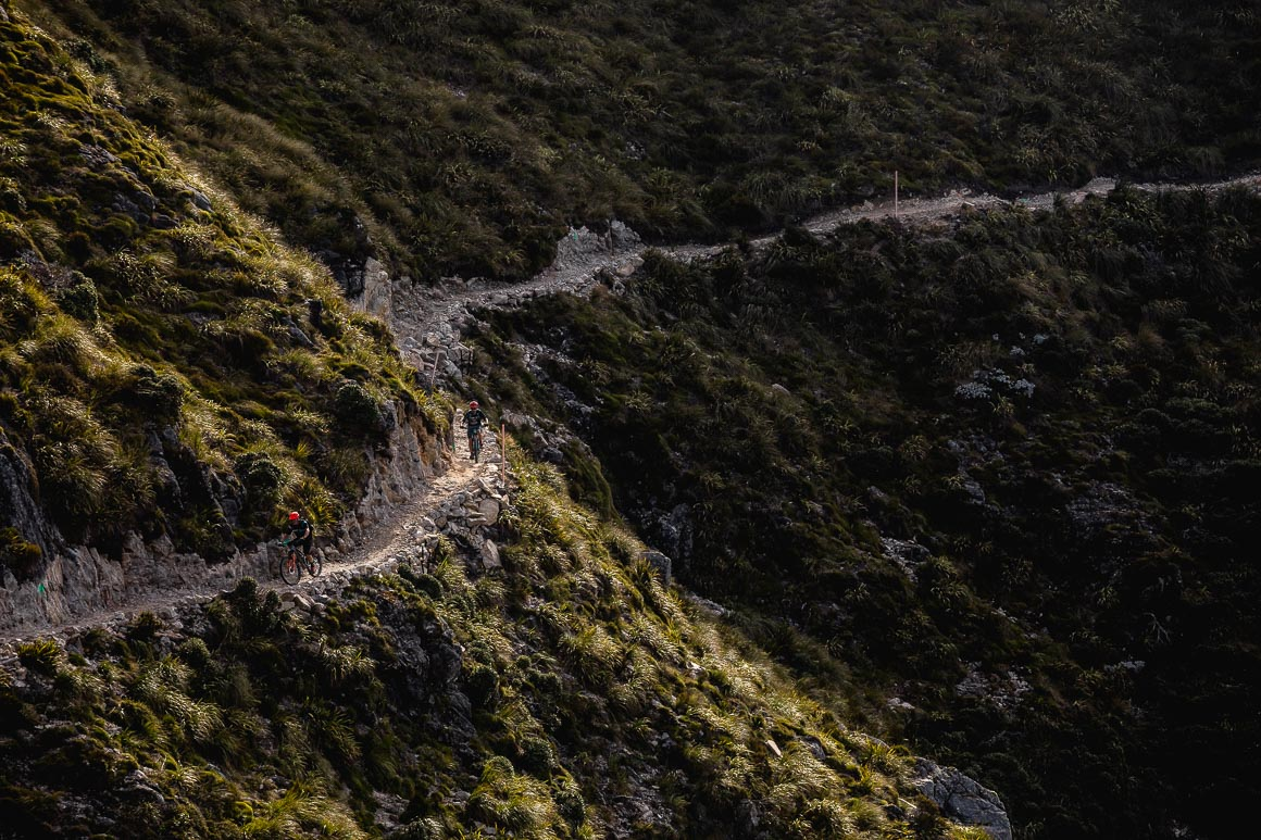 Mountain bikers negotiating an open traverse on The Old Ghost Road during a mountain bike tour New Zealand.