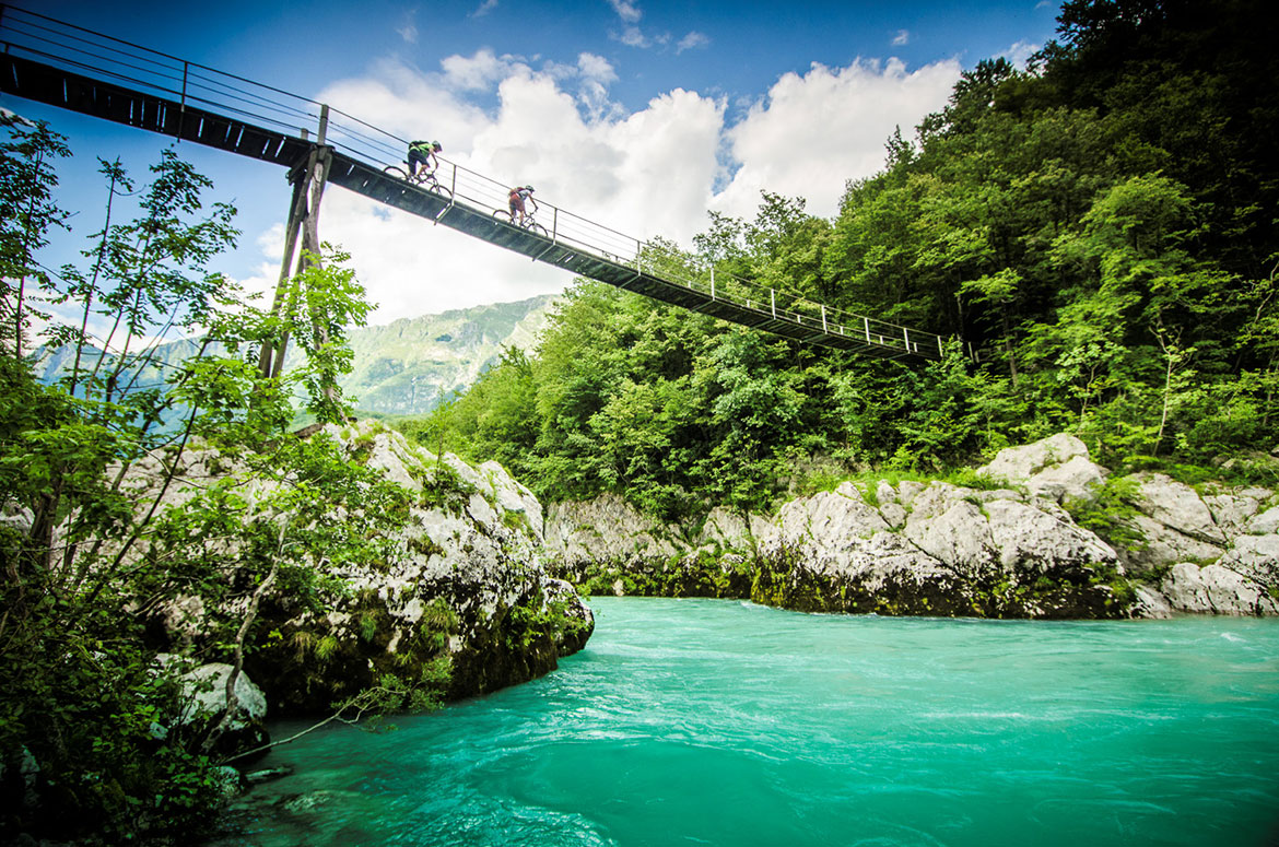 Crossing a mountain river in the Alps during a mountain bike tour Slovenia, one of our mountain biking adventures in Europe.