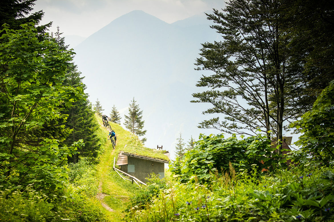 Mountain bikers racing through the countryside of Slovenia, one of our mountain biking adventures in Europe.