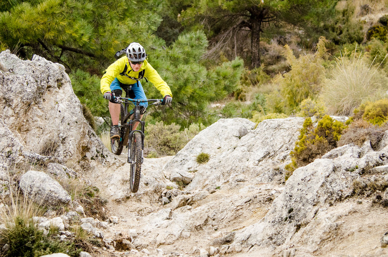 Mountain biker descending in the Sierra Nevada during a mountain bike tour Spain, one of our mountain biking adventures in Europe