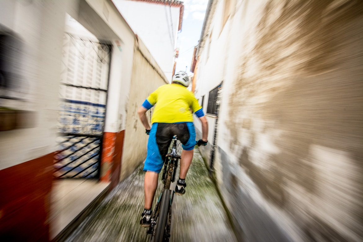 Riding through colourful alleyways in Andalucia during one of our mountain biking adventures in Europe.