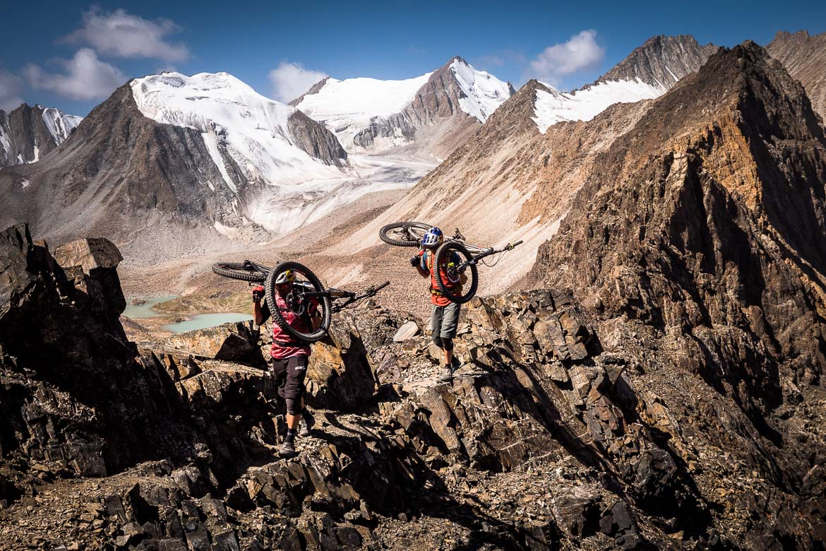 Carrying bikes on a craggy ridge whilst Mountain biking in Kyrgyzstan