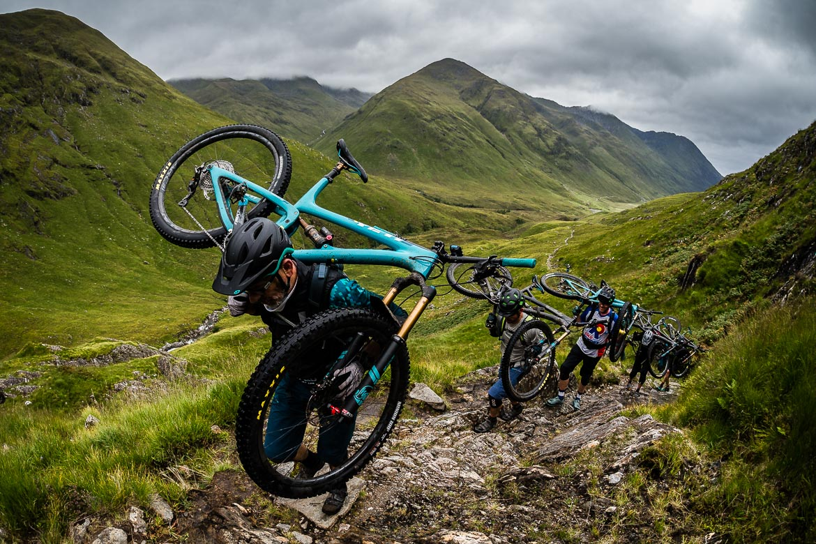 Carrying bikes up a climb during the Yeti Tribe Scotland.