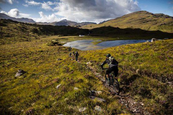 Riding towards a loch on a Mountain bike tour Torridon and Skye