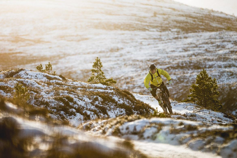 Local Aviemore mountain bike guide Chris Gibbs carving through the snow.