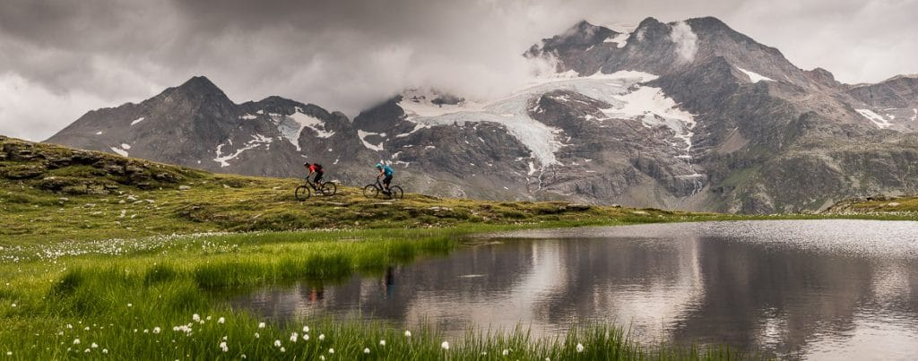 Riding alongside an alpine lake on a E-MTB Tour In Switzerland in photos