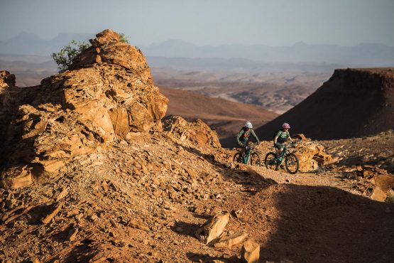 Pedalling between the rock formations on a mountain bike safari tour Namibia