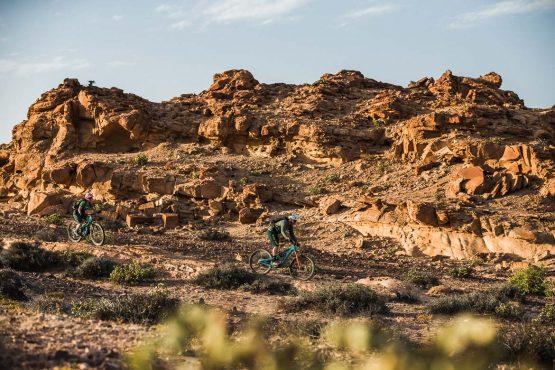 Riding past rocky outcrops on a mountain bike safari tour Namibia