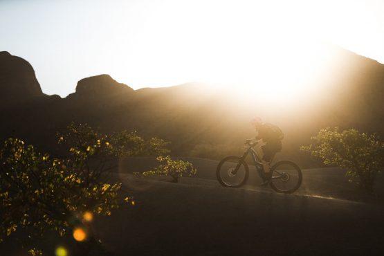 Climbing into the golden light on a mountain bike safari tour Namibia