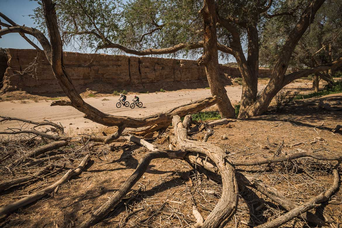 Riding through the dried up river bed on a E-MTB safari of Namibia