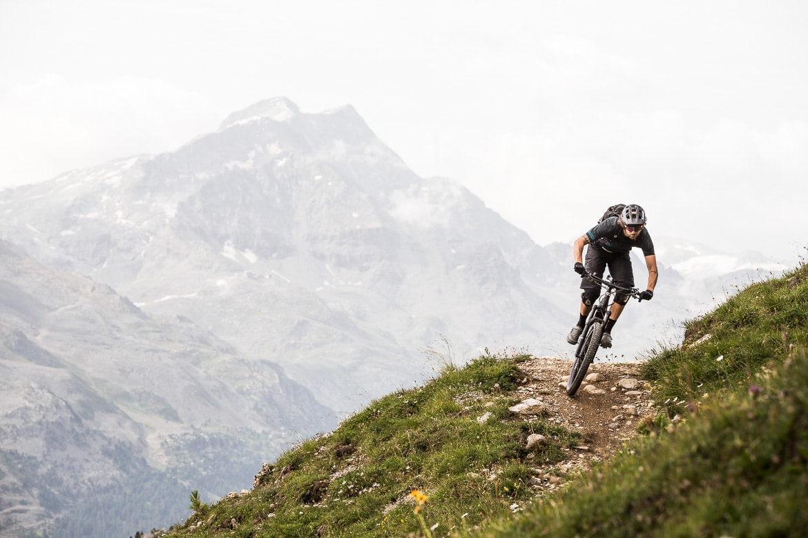 Shredding in front of jagged peaks whilst at home with local Swiss guide Dave Spielmann on a E-MTB tour in Switzerland