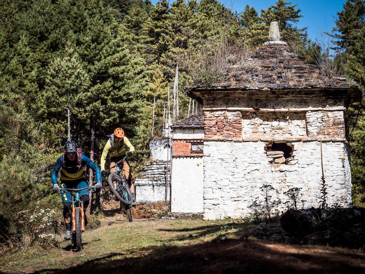 Blasting past trail side buildings whilst mountain biking in Bhutan